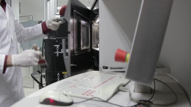 Dental technician opening the door of 3D printer to brush metal powder off