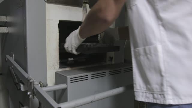 vídeos de stock, filmes e b-roll de técnico dental 3d de colocar implantes dentro da fornalha - fundir técnica de vídeo