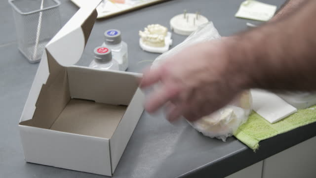 Dental technician putting plaster cast with tooth crowns in a box