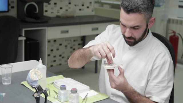 Dental technician putting tooth crown on a model abutment