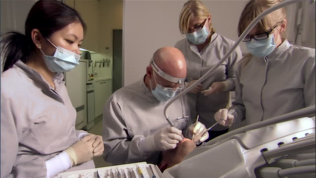 dentist administers bite-adjustment on man / dental assist - disposable gloves stock videos and b-roll footage