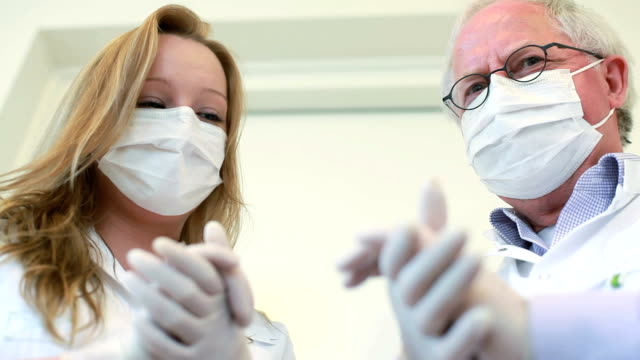 Dentist and assistant rubbing hands looking at the camera sinisterly