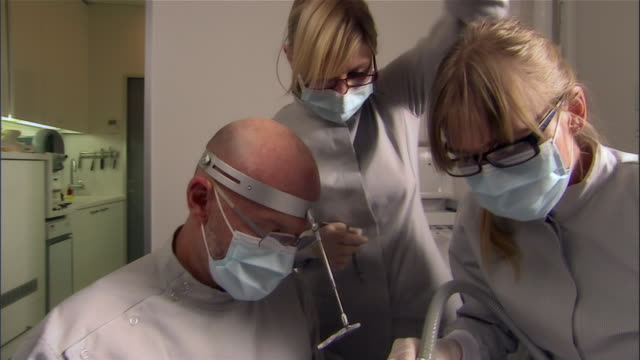dentist and dental assistants work on man - disposable gloves stock videos and b-roll footage