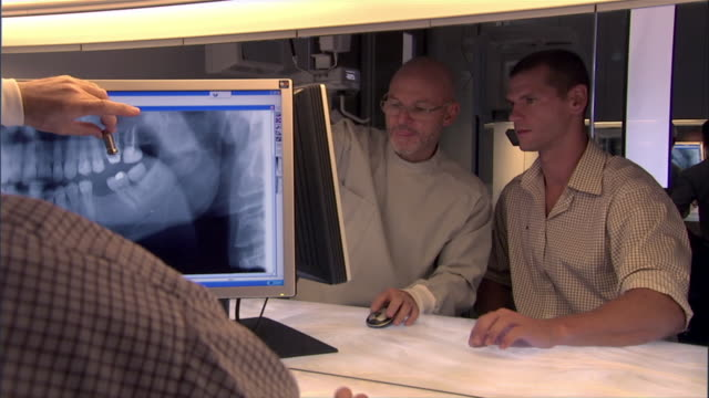 dentist and man sitting at desk, in consultation over dent - dental implants stock videos and b-roll footage