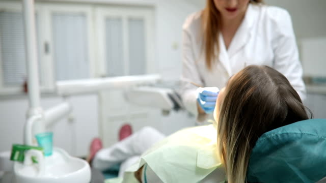 dentist curing a female patient - human teeth stock videos and b-roll footage