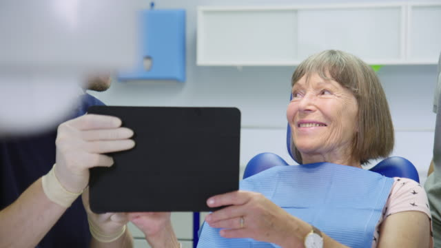 dentist discussing with senior patient over tablet - dental health stock videos & royalty-free footage