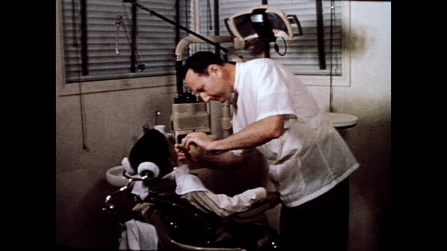 / dentist examines child sitting in dental chair / cu dentist concentrating levittown pa dentist's office on january 01 1958 in levittown pennsylvania - levittown pennsylvania stock videos and b-roll footage