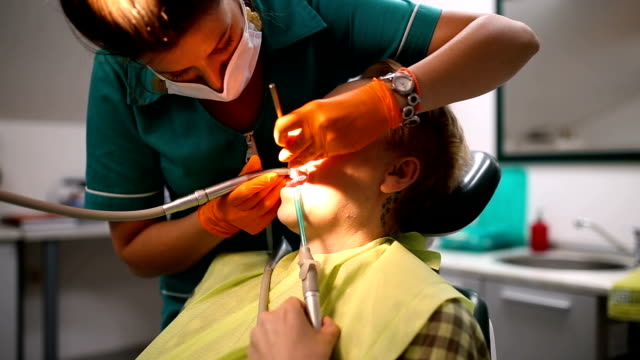 dentist examining a patient's teeth in the dentist. - disposable gloves stock videos and b-roll footage