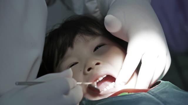 stockvideo's en b-roll-footage met tandarts die een patiënt tanden onderzoekt - beschermende handschoen