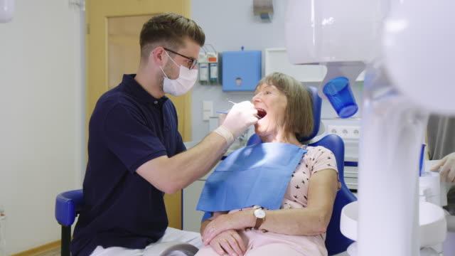 dentist examining senior woman's teeth in hospital - dental stock videos & royalty-free footage
