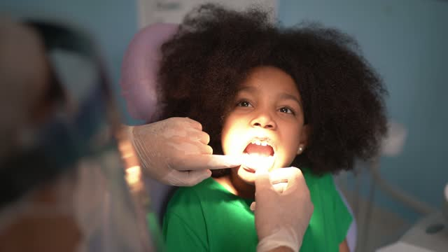 dentist examining teeth of child sitting in dentist chair - mouth open stock videos & royalty-free footage