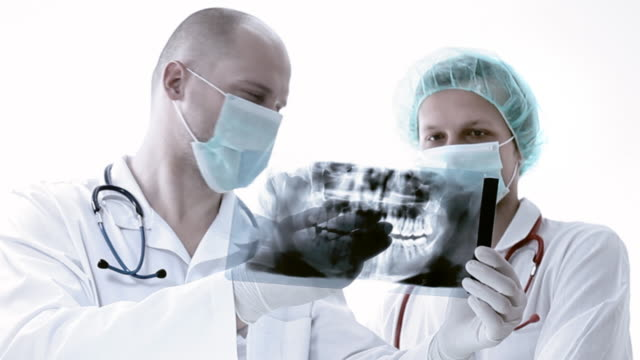 dentist examining x-ray image - protective mask workwear stock videos and b-roll footage