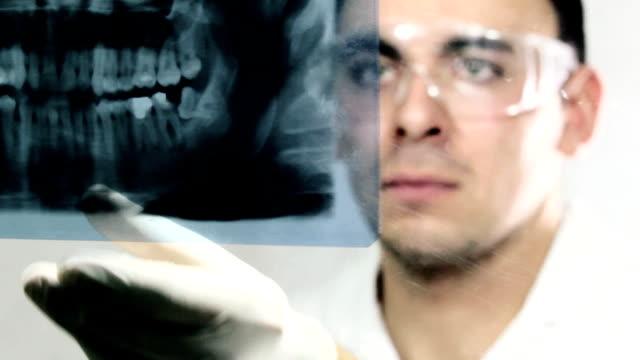 stockvideo's en b-roll-footage met dentist examining x-ray image - menselijk gebit