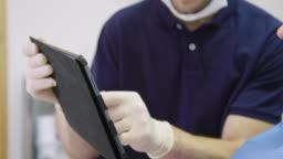 Dentist explaining patient over digital tablet