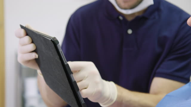 dentist explaining patient over digital tablet - rubber glove stock videos & royalty-free footage