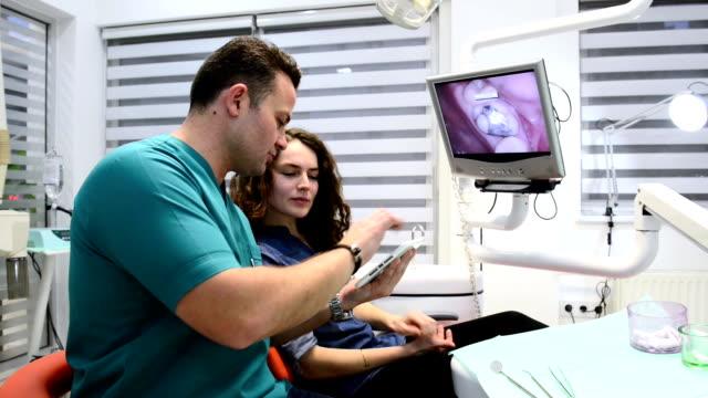 dentist informing patient via digital tablet - dentist's office stock videos and b-roll footage
