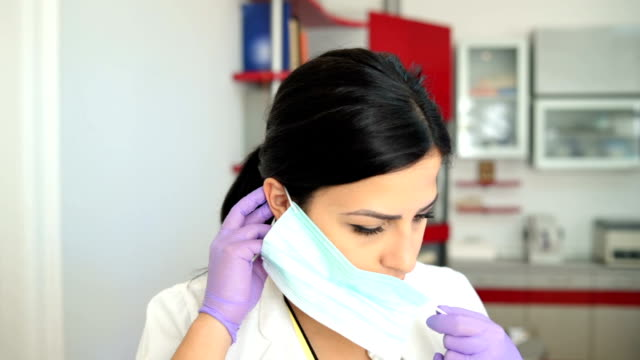 Dentist putting on surgical mask