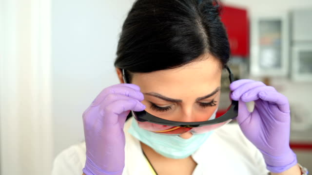 Dentist putting protective eyeglasses