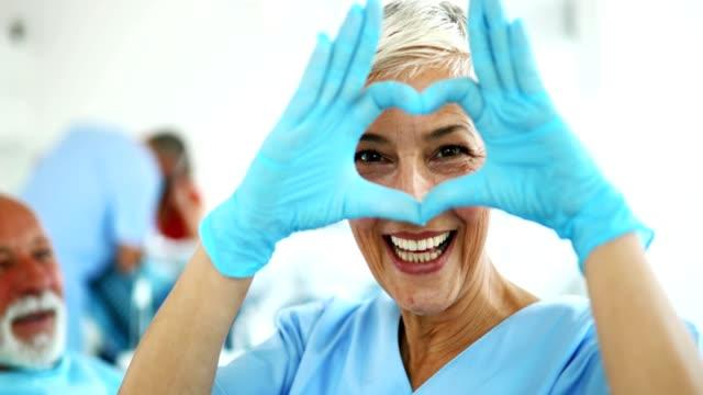 tandläkaren visar heart-symbolen. - kommunikationssätt bildbanksvideor och videomaterial från bakom kulisserna