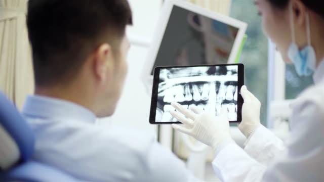 zahnarzt zeigt seinem patienten zähne röntgen - zahnarzt stock-videos und b-roll-filmmaterial