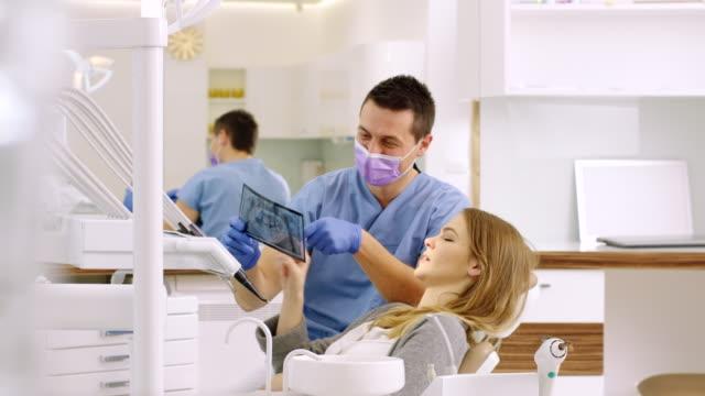 tandläkaren visar röntgen till kvinna - tandläkare bildbanksvideor och videomaterial från bakom kulisserna