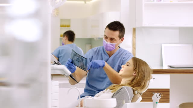 dentist showing x-ray to woman - x ray image stock videos & royalty-free footage