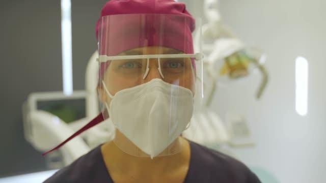 dentist smiling behind kn95l mask and protection screen - endast unga kvinnor bildbanksvideor och videomaterial från bakom kulisserna