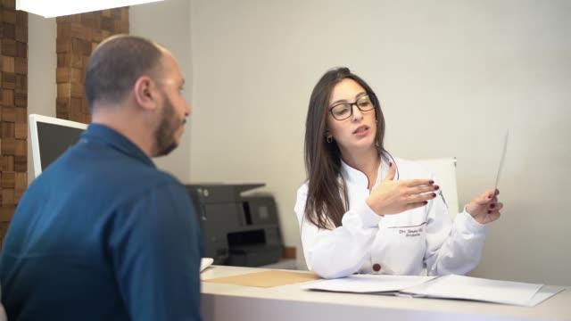 vídeos de stock, filmes e b-roll de dentista que fala sobre a imagem do raio x ao paciente - saúde dental