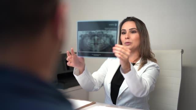 vídeos de stock, filmes e b-roll de dentista que fala sobre a imagem do raio x ao paciente - visita