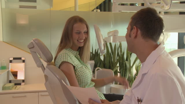 ms pan dentist talking to female patient/ berlin, germany - dentist stock videos & royalty-free footage