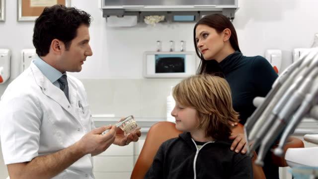 dolly hd: dentista insegnando un ragazzo come lavarsi i denti - dentista video stock e b–roll