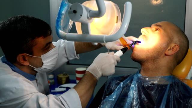 stockvideo's en b-roll-footage met dentist treating a patient - beschermende handschoen