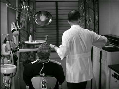 b/w 1945 rear view dentist treating male patient in office - dentist stock videos & royalty-free footage
