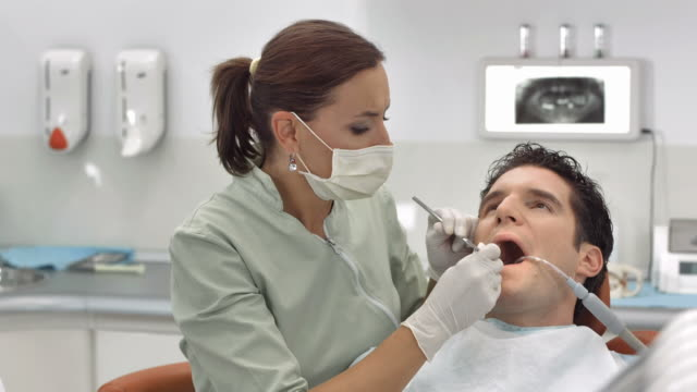 hd dolly: dentist treating patient's teeth - dental hygiene stock videos & royalty-free footage