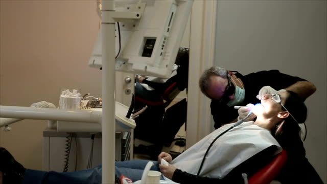 Dentist using a modern diode dental laser for periodontal care. Patient wearing protective glasses, preventing eyesight damage.