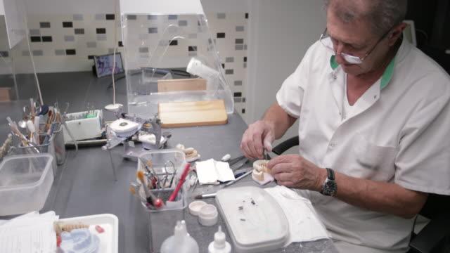 vidéos et rushes de dentiste à l'aide de vis pour percer des trous dans les dents sur moule dentaire - 60 64 ans