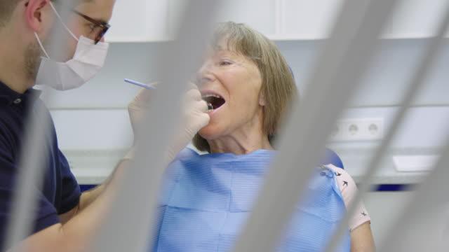 vídeos de stock e filmes b-roll de dentist with medical equipment examining woman - dentista
