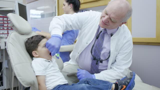 vidéos et rushes de dentiste travaillant sur un petit enfant assis dans un fauteuil dentaire dents gommage ses - dents