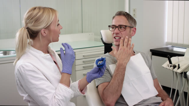 dentist's office - male patient with greying hair and glasses lies on dentist's chair while female doctor dentist with long blonde hair wearing doctor's white coat describes the procedure of whitening bleaching teeth while showing lip cheek retractor. - teeth whitening stock videos and b-roll footage