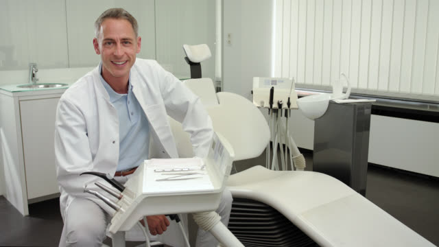 dentist's office - mid adult dentist doctor with short greying hair and a toothy smile in light blue polo shirt and white medical scrubs doctor's coat with a big trustful toothy smile looking at camera surrounded by dental equipment, locked camera. - polo shirt stock videos & royalty-free footage