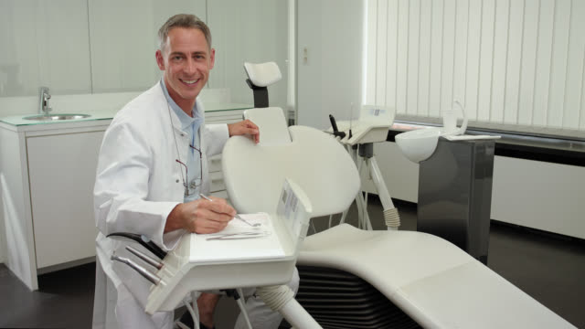 Dentist's office - mid adult dentist with short greying hair and a toothy smile in blue polo shirt and white medical scrubs doctor's coat and glasses hanging around his neck with a big toothy smile looking at camera holding dental mirror, locked camera
