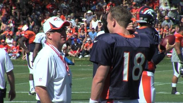 Denver Broncos head coach John Fox talks with quarterback Peyton Manning during practice at training camp Broncos coach John Fox with Peyton Manning...