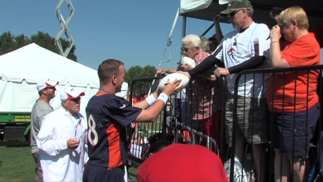 Denver Broncos quarterback Peyton Manning signs autographs and warms up before the second day of training camp Peyton Manning signing autographs at...