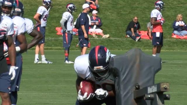 Denver Broncos running backs practice during training camp hitting a practice dummy and catching passes