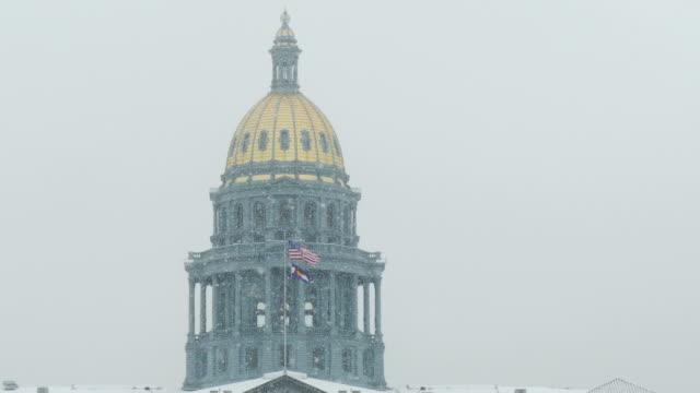 Denver Colorado State Capitol Building gold dome winter snow flags