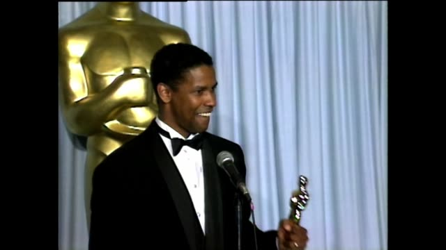 Denzel Washington holds Academy Award while speaking to the press about his Best Supporting Actor Academy Award for the film Glory at the 1990...