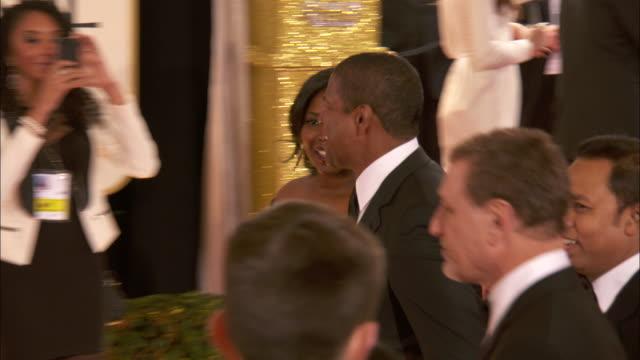 Denzel Washington w/daughter Olivia Washington smiling and waving walking down the red carpet at the Beverly Hilton Hotel