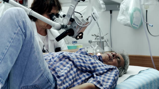 ENT department in hospital. Doctor examines patient's ear