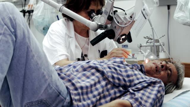stockvideo's en b-roll-footage met ent afdeling in het ziekenhuis. dokter onderzoekt oor van de patiënt - tanden op elkaar klemmen