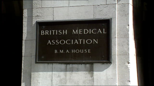 lighted windows negotiators london seen seated inside whitehall day tavistock 0350 sign on wall 'british medical association bma square house'... - patientin stock-videos und b-roll-filmmaterial